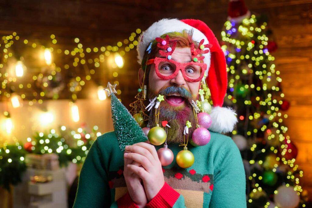 Ein Man mit Weihnachtskugeln auf sein Bart demonstriert der Papa Baum