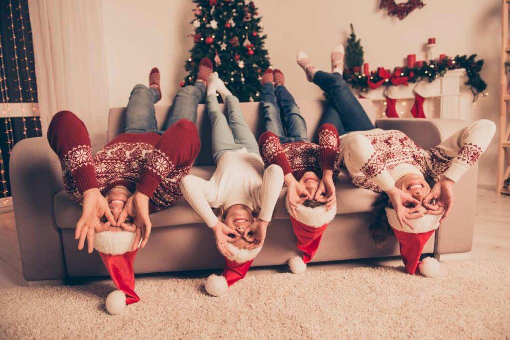 Familie probieren lustige Weihnachtsfoto Ideen aus auf dem Sofa